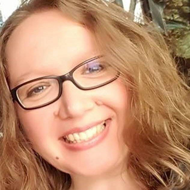 Woman with curly dark blonde hair and black glasses, tilting her head and smiling.