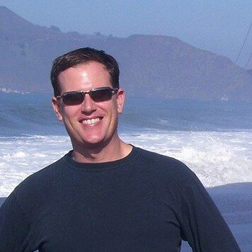 Man with dark brown hair and sunglasses standing in front of the ocean