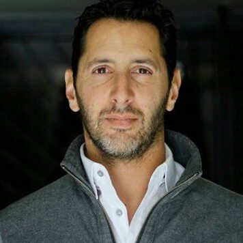 A man with dark hair and a scruffy beard, wearing a white button up with a gray sweater over it.